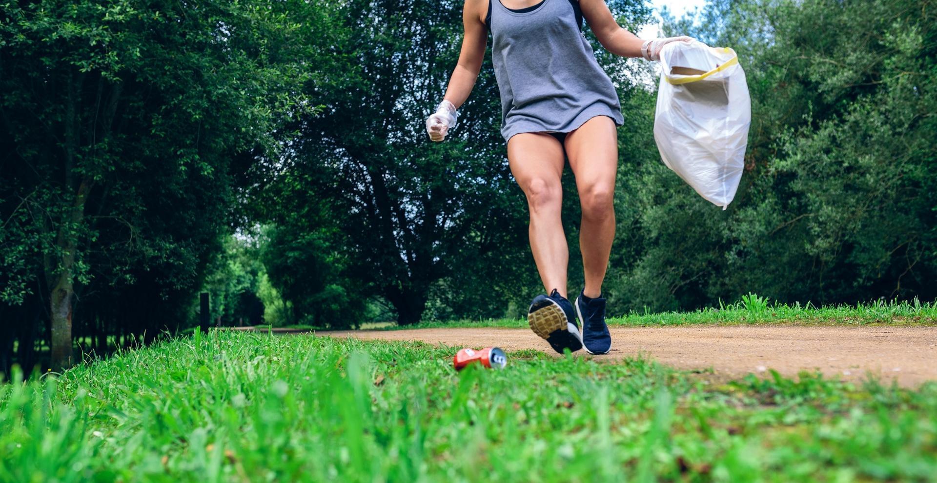 Une femme court et ramasse des déchets dans la nature