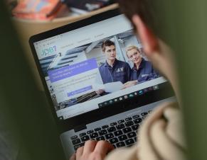 Une personne devant son ordinateur cherchant un emploi sur job77