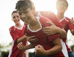 Des jeunes portant des maillots de foot en train de chahuter