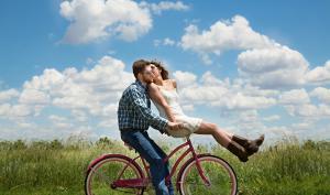 Deux jeunes sur un vélo qui s'embrassent