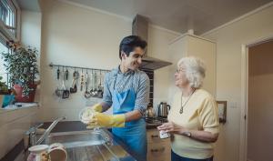Jeune homme faisant le ménage au domicile d'une personne âgée