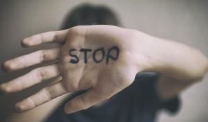 Gros plan sur une main sur laquelle est écrit STOP
