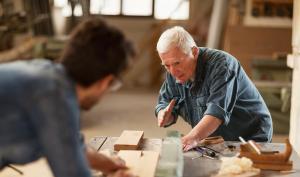 Dans un atelier d'ébénistes, un homme âgé montre une tâche à un jeune homme flouté