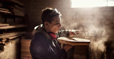 Un jeune artisan du bois souffle sur une pièce qu'il vient de terminer