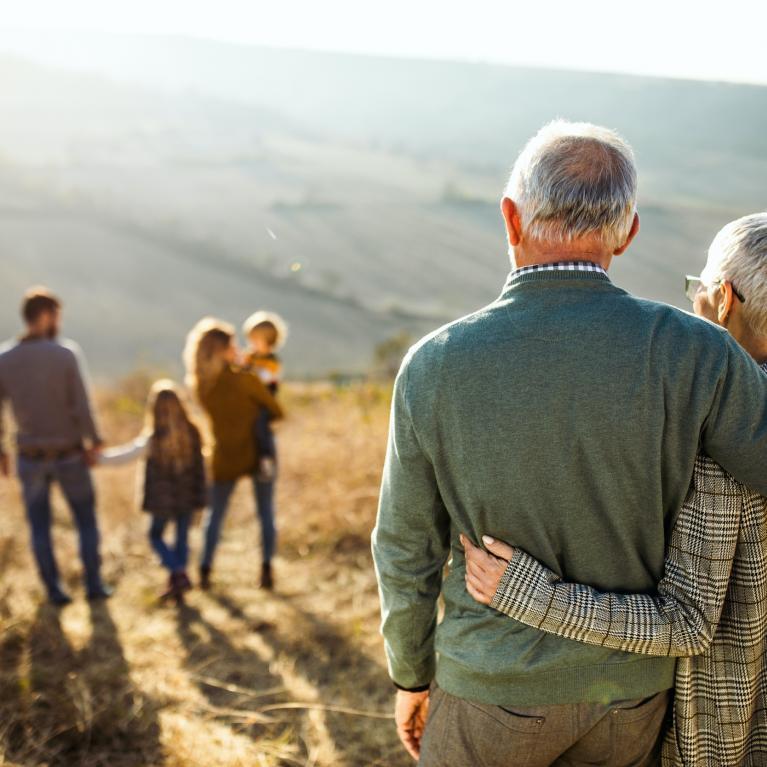 Au 1er plan un couple de personnes âgées enlacées de dos regarde au loin un jeune couple avec 2 enfants