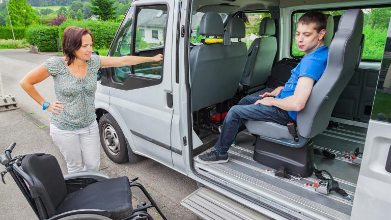 Une femme en train de faire descendre un enfant handicapé sur son fauteuil roulant